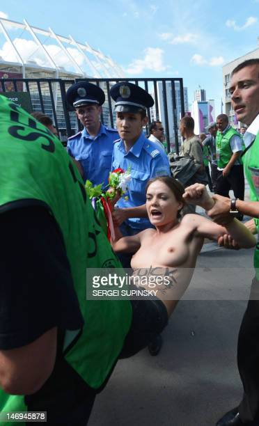 Policemen detain Femen activist Oksana Shachko as she protests topless at the entrance gates of the Olympic stadium in Kiev on June 24 2012 The half...
