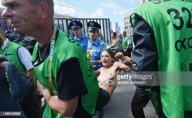 Policemen detain Femen activist Oksana Shachko as she protests topless at the entrance of the Olympic stadium in Kiev on June 24 2012 The half naked...