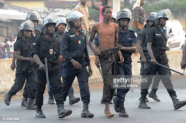 TOPSHOT Policemen escort a demonstrator in an empty street of Conakry on February 15 on the day of a nationwide general strike in Guinea with unions...