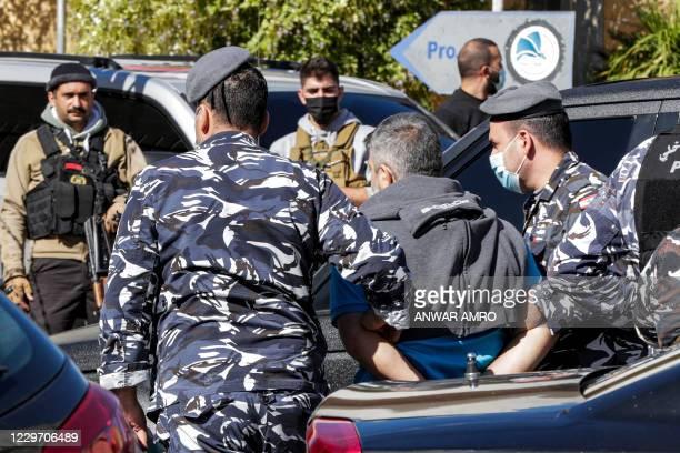 Policemen escort a prisoner who had fled a detention centre earlier upon recapture, in Baabda, east of Lebanon's capital Beirut, on November 21,...
