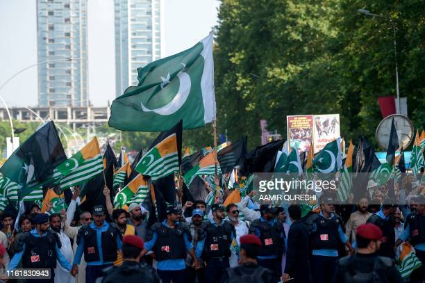 Policemen escort a protest rally near the Indian High Commission in Islamabad on August 15 as the country observes a 'Black Day' on India's...