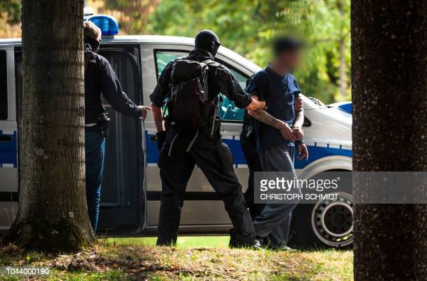 Policemen escort a suspected rightwing terrorist after arriving at the Federal Supreme Court in Karlsruhe southwestern Germany on October 1 2018...