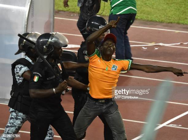 Policemen escort an angry supporter at the Felix HouphouetBoigny stadium in Abidjan on November 11 at the end of the FIFA World Cup 2018 Africa Group...