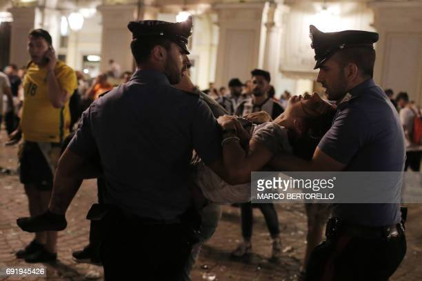 Policemen evacuate a Juventus' supporter in Piazza San Carlo during a panic movement in the fanzone where thousands of Juventus fans were watching...