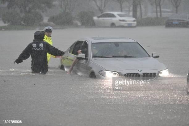 Policemen evacuate traffic in floodwater near Zhengzhou Railway Station on July 20, 2021 in Zhengzhou, Henan Province of China. Torrential rains hit...
