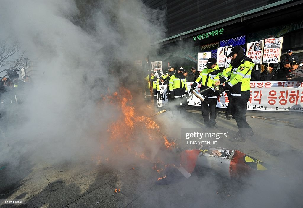 Policemen extinguish a fire after South Korean conservative activists burnt an effigy of North Korean leader Kim Jong-Un during a rally denouncing North Korea's nuclear test, in Seoul on February 13, 2013. South Korea said on February 13 it would accelerate the development of longer-range ballistic missiles that could cover the whole of North Korea in response to a third nuclear test by Pyongyang.