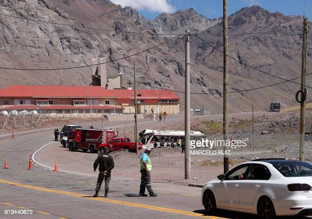 Policemen firefighters and soldiers work at the scene after a bus carrying teenagers from a Chilean football school crashed into another bus on its...
