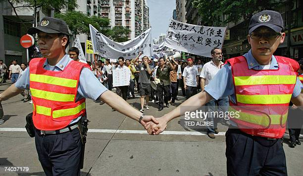 Policemen form a human barricade as thousands of protesters carrying banners march through the streets during a May Day demonstration against labour...
