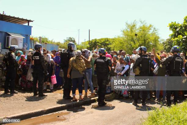 TOPSHOT Policemen from the French Gendarmerie contain protesters as they secure the airport area during the arrival of French Overseas Minister on...