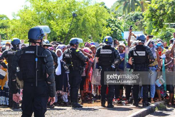 Policemen from the French Gendarmerie contain protesters as they secure the airport area during the arrival of French Overseas Minister on March 12...