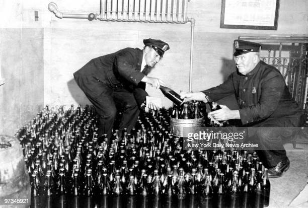 Policemen Goldinger and Faulkner check over 500 bottles of home brew seized in Rockaway Beach speakeasy raid by men from the 15th Inspection District