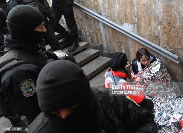 Policemen guard a participant of a transgender rights march as doctors provide medical care after an attack by far-right groups activists in Kiev on...
