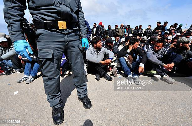 Policemen guard Tunisians wouldbe immigrants who are waiting to be identified on the Italian island of Lampedusa on March 29 2011 Tension is rising...