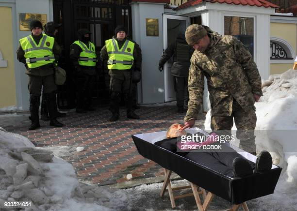 Policemen guarding the General the Consulate of Russia in the Ukrainian city of Kharkiv watch an Ukrainian activist touching the nose of a dummy...