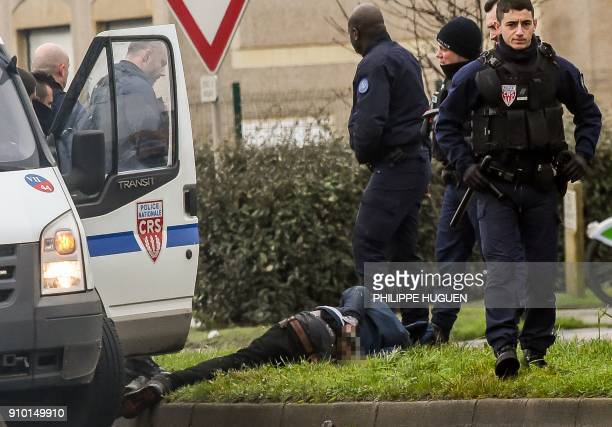 TOPSHOT Policemen have just arrested a migrant on January 25 2018 in the French northern city of Calais / AFP PHOTO / PHILIPPE HUGUEN
