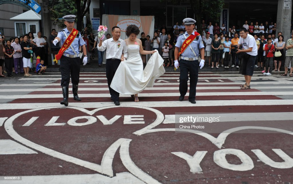 Policemen help a couple cross the 'Love Zebra Crossing' during a disabled persons group wedding held to mark the Qixi Festival, the Chinese equivalent of Valentine's Day on August 26, 2009 in Chengdu of Sichuan Province, China. Thirteen coulples from five districts of Chengdu attended the ceremony. The Qixi Festival, also known as the Double Seventh Festival, falls on the seventh night of the seventh lunar month. The festival originates from a romantic legend of lovers, the cowherder Niulang and fairy Zhinu, who were separated by the Supreme God but reunited across the Milky Way once a year on the day.