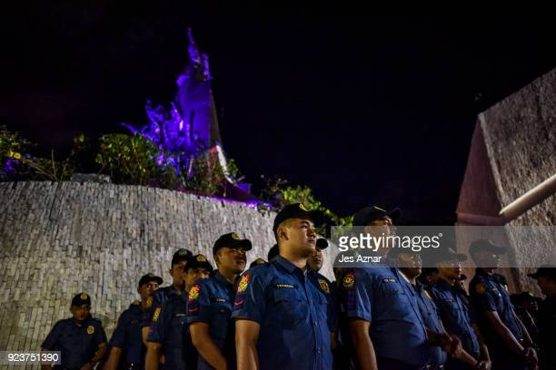 Policemen hold a formation in front of the People Power Monument during the 32nd annual commemoration of the EDSA People Power uprising on February...