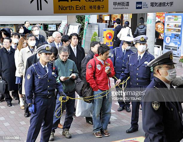 Policemen hold back commuters as they for train services to resume at Tokyo's Chofu station on March 14, 2011 as rail services around the capital...