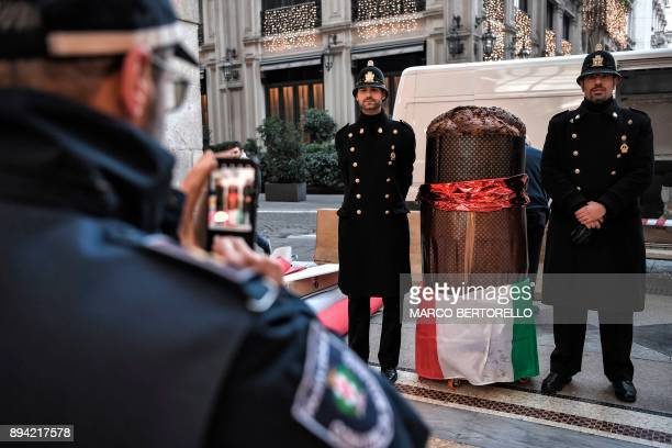 Policemen in high uniform pose next to a giant 'Panettone' on December 17 2017 in the Vittorio Emanuele II gallery in Milan The Panettone a typical...