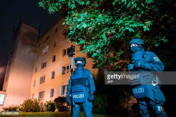 Policemen in protective cllothing stand in front of at a residential building in Chemnitz eastern Germany on October 8 2016 Police found several...