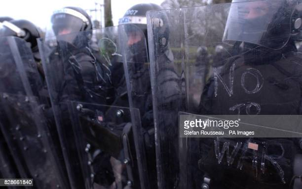 Policemen in riot gear stand at the entrance to Hillsborough village near Belfast to prevent peace protesters from reaching Hillsborough Castle where...