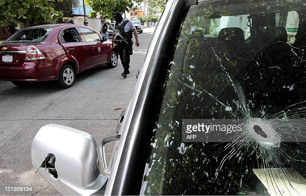 Policemen inspect the scene after a shooting between policemen and gunmen in the touristic city of Acapulco Guerrero state Mexico on August 18 2011 A...
