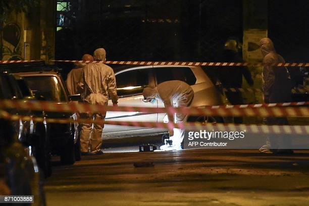 TOPSHOT Policemen inspect the street after a gunman fired riot police guarding the headquarters of the Greek Socialist Party Pasok in Athens on...