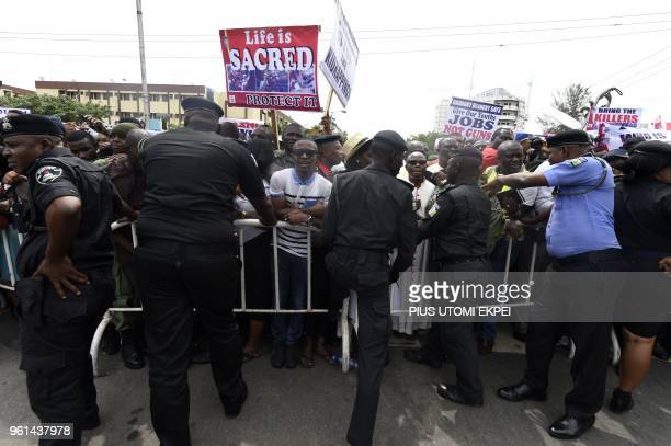 Policemen install a barrier to stop protesters from gaining the entrance of the government house during a solidarity march by Catholics to protest...