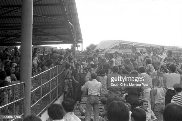 Policemen intervening to separate two groups of soccer fans following a friendly match between the visiting Middlesbrough team and Hong Kong's...