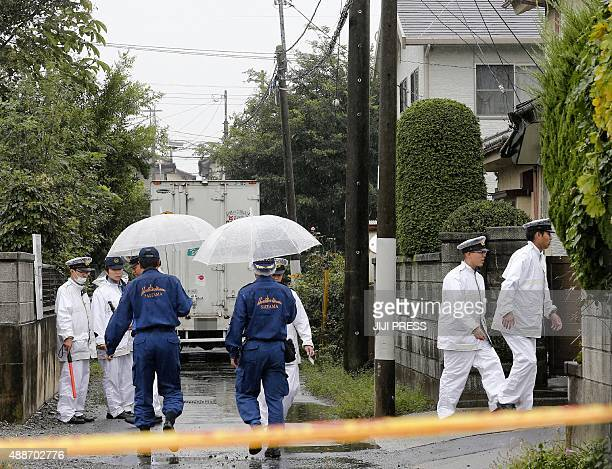 Policemen investigate the area around a murder scene in Kumagaya Saitama prefecture on September 17 2015 where six people were found stabbed to death...