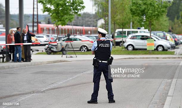 A policemen is seen behind the police cordon near the train station in Grafing near Munich southern Germany where a man killed one person and wounded...