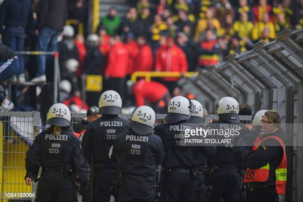 Policemen keep a close eye on Berlin fans who lite flares during the German first division Bundesliga football match BVB Borussia Dortmund v Hertha...