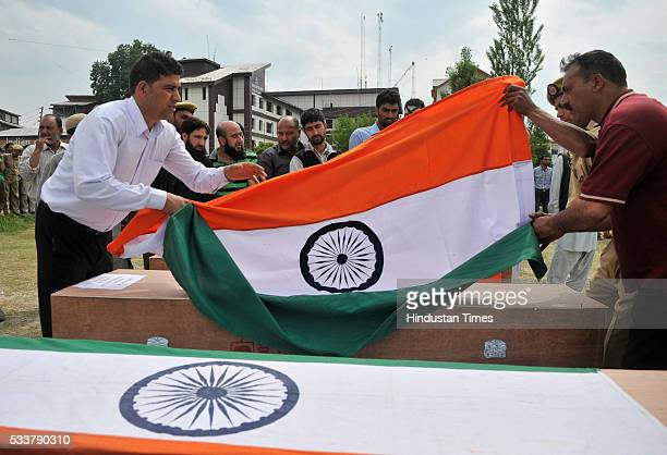 Policemen lay Indian tri-colour on the coffin of a policeman killed in terror attack during a wreath laying ceremony at Police Control Room on May...