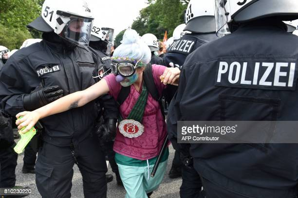 Policemen lead away a demonstrator dressed as a clown during a protest on July 7 2017 in Hamburg northern Germany where leaders of the world's top...