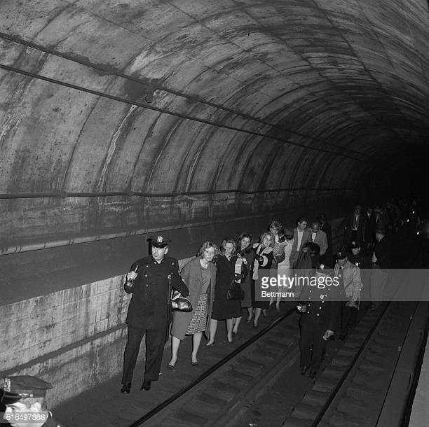 Policemen lead commuters through a subway tunnel where they were trapped late November 9th when power failure stopped all trains The black out...