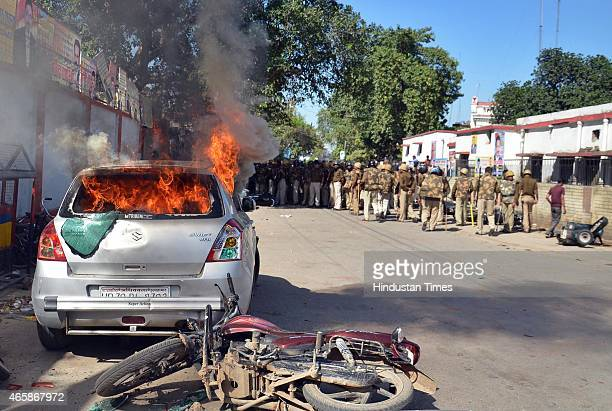 Policemen look as vehicle set alight by angry lawyers outside the district court after a police inspector shot a lawyer in the court premises on...