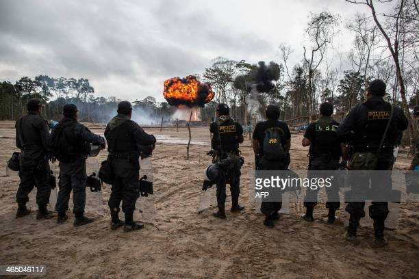 Policemen look at the destruction of camps and pumps used for illegal gold mining in Mega 13 Madre de Dios region Peru on January 25 during an...