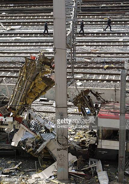 Policemen look for clues around a train after it exploded at the Atocha train station in Madrid 11 March 2004 At least 185 people were killed and...