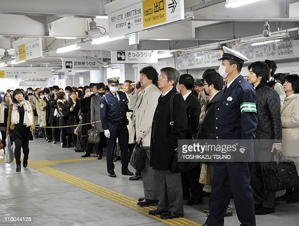 Policemen look on as commuters wait for train services to resume at Tokyo's Chofu station on March 14, 2011 as rail services around the capital were...