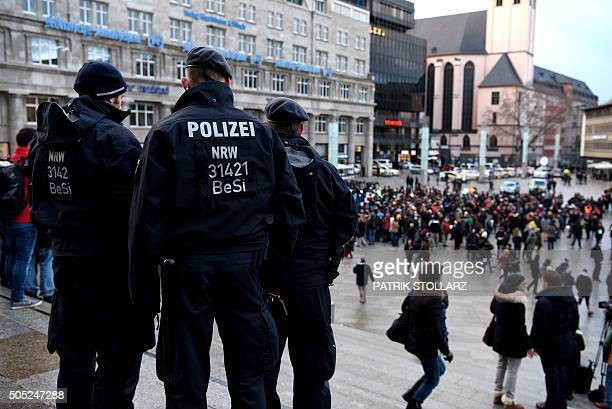 Policemen look on as refugees from Syria demonstrate against violence near the Cologne main train station in Cologne western Germany on January 16...