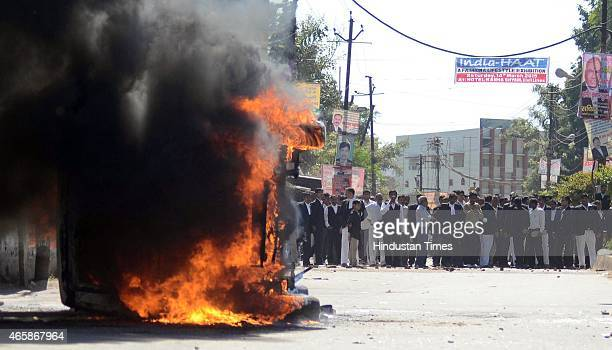 Policemen look on as vehicle set alight by angry lawyers outside the district court after a police inspector shot a lawyer in the court premises on...