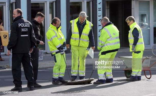 Policemen look on as workers lift a manhole cover as security measures are undertaken on September 26 2018 in preparation of the state visit of the...