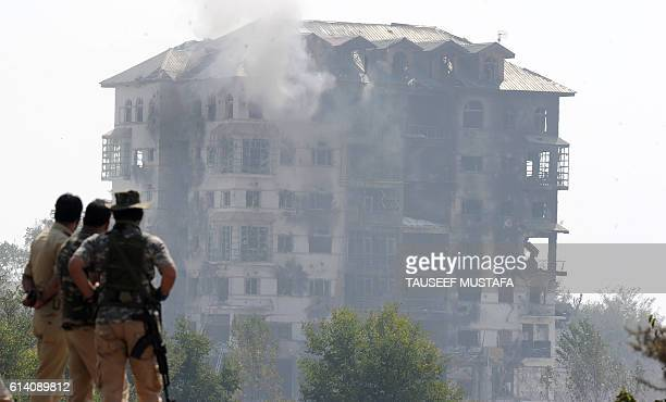 Policemen look towards a building where suspested militants are thought to be hiding on the third day of a gunfight between the Indian army and...