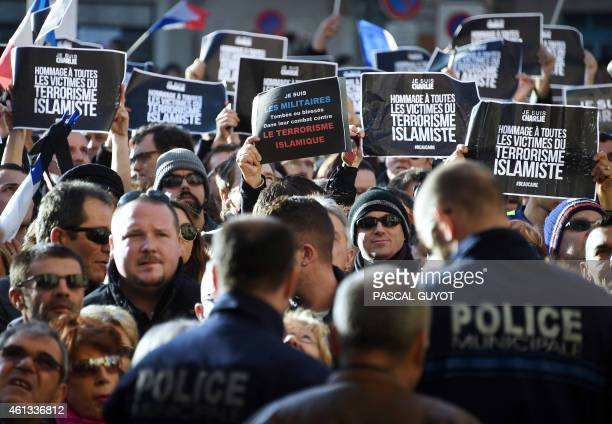 Policemen looks on as people hold signs reading 'Tribute to all the Islamic terrorism victims' during a Unity rally Marche Republicaine on January 11...