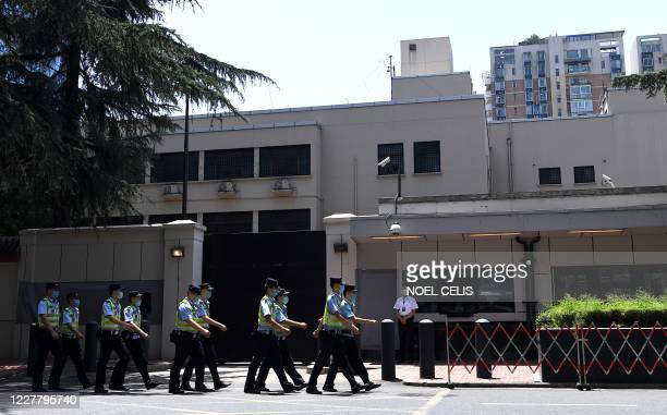 Policemen march in front of the US Consulate in Chengdu, southwestern China's Sichuan province on July 27, 2020. - Chinese authorities took over the...