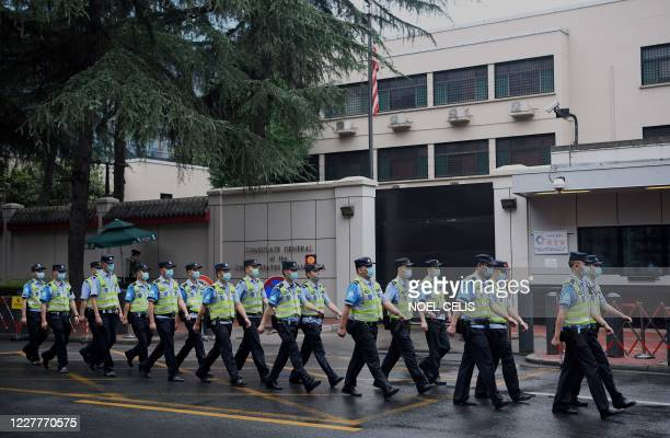 Policemen march past the US consulate in Chengdu, in Sichuan province on July 25, 2020. - Staff at the US consulate in the Chinese city of Chengdu...