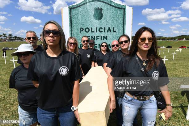 Policemen mock a funeral during a protest by Police Union members against the pension system reform in front of the National Congress in Brasilia on...