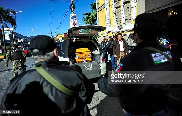 Policemen observe as the coffin with the remains of journalist Anabel Flores Salazar is loaded into a hearse after a mass at the church in Orizaba...