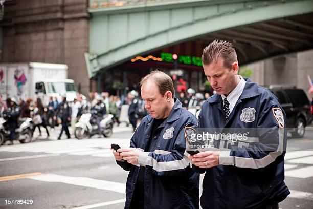 Policemen on 42nd street using their mobile phone, New York