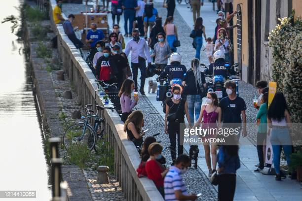 Policemen on motorbikes patrol as people stroll and have a drink along a canal in the Navigli district of Milan on May 21 2020 as the country eases...